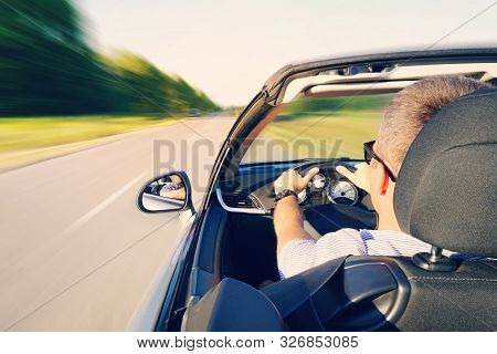 Man Driving A Convertible Car On Country Road. View From The Inside Behind The Driver. Man Is Drivin