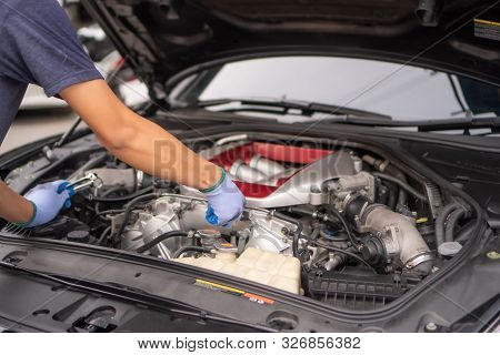 Professional Mechanic Checking Car Engine ,auto Mechanic Working In Garage. Repair Service.