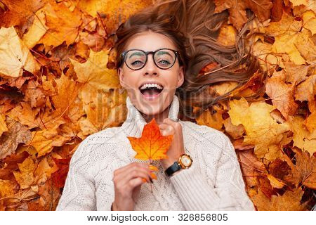 Funny Young Hipster Woman In A Fashionable Knitted Sweater In Stylish Glasses With An Orange Leaf In