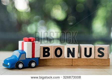 Mini Toy Truck With Gift Box Near Letter Block In Word Bonus. Yearly Bonus Concept. Bonus Is Motivat