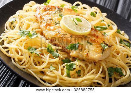 Cooked Chicken Francaise With Spaghetti In Lemon Wine Gravy Close-up On A Plate. Horizontal