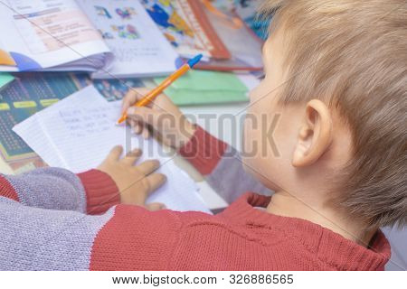A Boy Writes English Words By Hand On Traditional White Paper In A Notebook. The Boy Writes His Firs