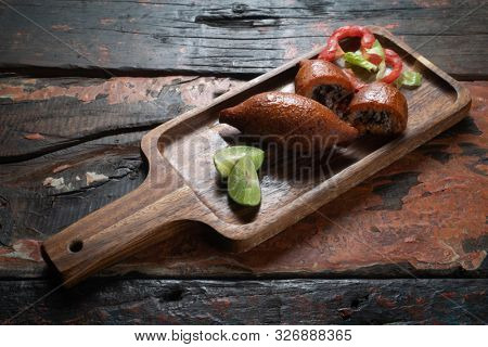Arabic meat appetizer kibbeh isolated on rustic wooden table