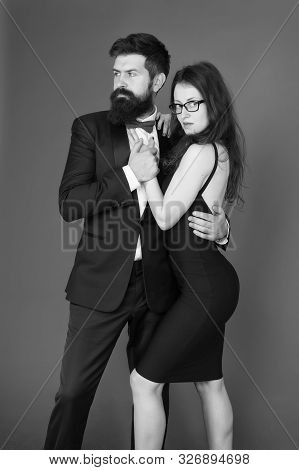 Couple Man In Tuxedo And Elegant Girl. Man Bearded Hipster And Woman In Formal Dress Red Background.