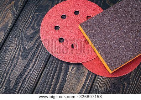 Set of abrasive tools and sandpaper different colors on black vintage wooden backgroundgrinding items poster