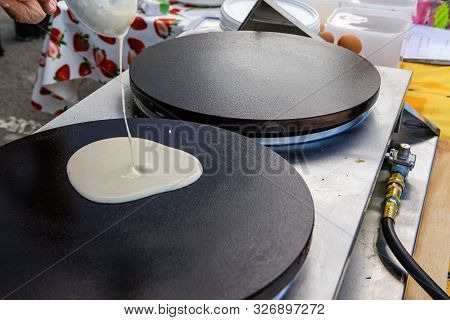 A Closeup View Of Pancake Batter Being Poured Onto A Hotplate At A Food Vendor Stall During A Fair F