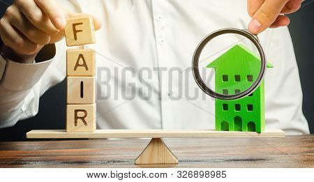 Wooden Blocks With The Word Fair And A Wooden House. Fair Value Of Real Estate And Housing. Property