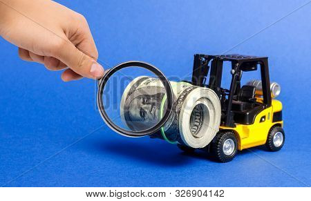 A Magnifying Glass Looks At A Forklift Truck Carries A Bundle Of Dollars. Attracting Direct Investme
