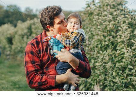 Caucasian father hugging kissing baby boy. Parent holding carrying child son. Authentic lifestyle touching tender moment. Single dad family life concept. Happy fatherhood concept. poster
