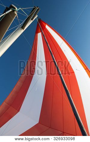 White-red Developing Sail On A Yacht Mast Against The Blue Sky, Bottom View. Traveling By Sea On Sun