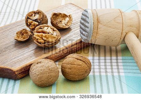 Cracked Walnuts (juglans Regia) Near Wooden Meat Mallet On A Brown Wooden Board. Natural Unbleached
