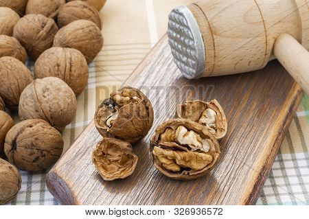 Whole And Cracked Walnuts (juglans Regia) Near Wooden Meat Mallet On A Brown Wooden Board. Natural U