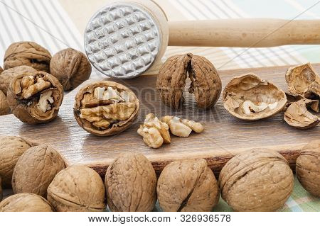 Front View Of Whole And Cracked Walnuts (juglans Regia) Near Wooden Meat Mallet On A Brown Wooden Bo