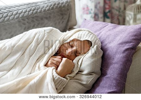 Sick Young Woman Slleping, Lying On Sofa, Wrapped In Wool White Plaid, Tries To Warm Herself, Having