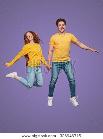 Full Body Excited Man And Woman In Similar Clothes Holding Hands And Smiling While Leaping Up And Ha
