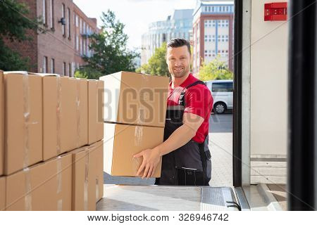 Portrait Of A Smiling Mover In Uniform Loading A Cardboard Boxes In A Moving Van
