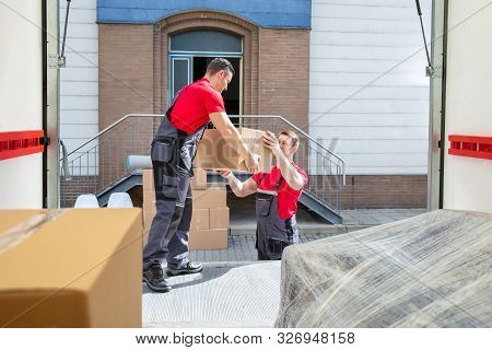 Young Male Movers Unloading The Cardboard Boxes In The Van Outside The House
