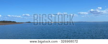 Blue Sky Nautical Tropical Island Waterscape Landscape Scene With White Fluffy Cumulus Clouds And Mo