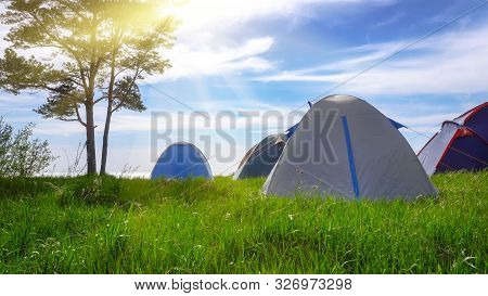 A Tent Camp By The Sea, The Sun Rays Through The Branches Of The Trees. The Concept Of A Pleasant Fa