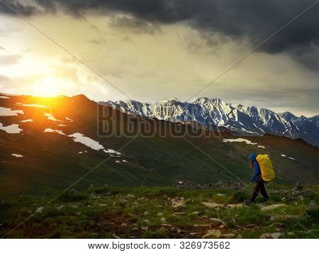 A Tourist In Rainy Weather Walks Along The Trail To The Top Of The Mountain. The Focus On The Far Ba