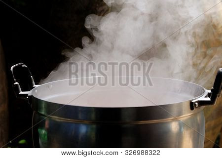 White Smoke From A Hot Cooking Pot In Kitchen Area With Dark Background