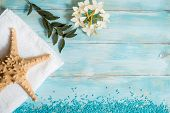 Spa and wellness setting with flowers, and white towel on old wooden background. Blue dayspa nature set. copyspace. Vacation concept. flat lay. top view. poster