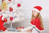 Child decorating christmas tree with red balls ornaments. Girl kid decorating christmas tree. Cherished holiday activity. Kid in santa hat decorating christmas tree. Family tradition concept poster