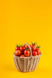 Basket With Tomatoes On A Yellow Background.