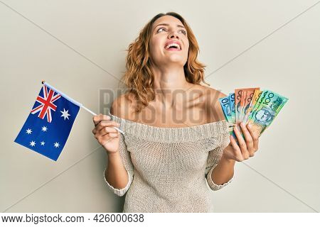 Young caucasian woman holding australian flag and dollars smiling and laughing hard out loud because funny crazy joke.