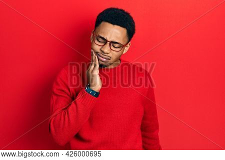 Young african american man wearing casual clothes and glasses touching mouth with hand with painful expression because of toothache or dental illness on teeth. dentist