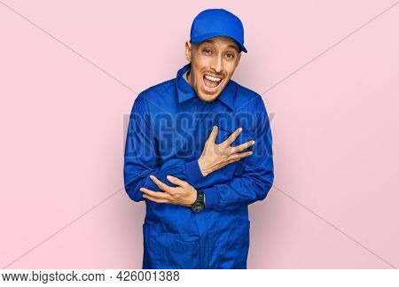 Bald man with beard wearing builder jumpsuit uniform smiling and laughing hard out loud because funny crazy joke with hands on body.