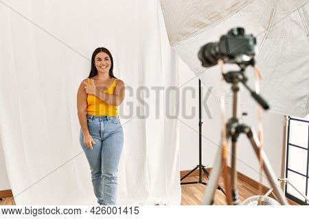 Young beautiful hispanic woman posing as model at photography studio cheerful with a smile of face pointing with hand and finger up to the side with happy and natural expression on face