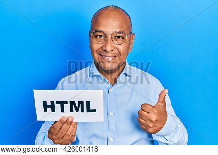 Middle age latin man holding html paper message smiling happy and positive, thumb up doing excellent and approval sign