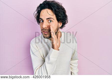 Handsome hispanic man wearing casual white sweater hand on mouth telling secret rumor, whispering malicious talk conversation