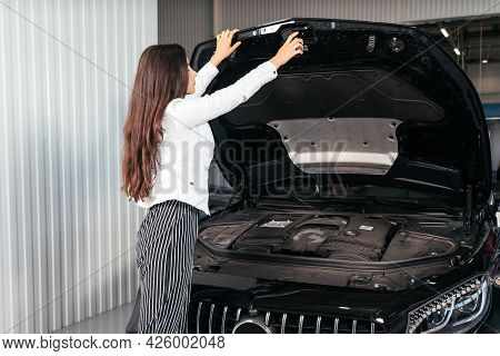 Young Woman With Opened Hood In Garage Looking Under Car Hood