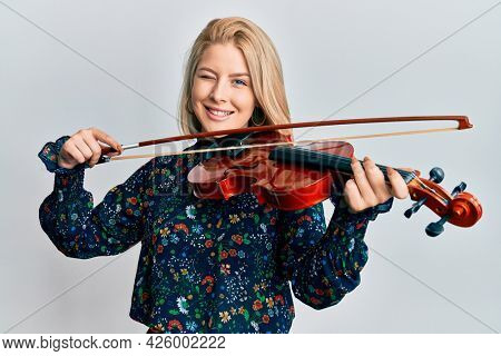 Young blonde woman playing violin winking looking at the camera with sexy expression, cheerful and happy face.
