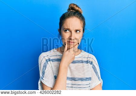 Young blonde woman wearing casual striped t shirt thinking concentrated about doubt with finger on chin and looking up wondering