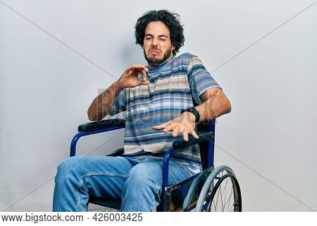 Handsome hispanic man sitting on wheelchair disgusted expression, displeased and fearful doing disgust face because aversion reaction.