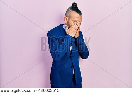Young hispanic man wearing business suit and tie rubbing eyes for fatigue and headache, sleepy and tired expression. vision problem