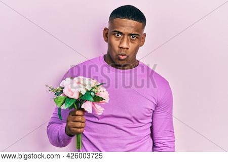 Young black man holding bouquet of white flowers scared and amazed with open mouth for surprise, disbelief face