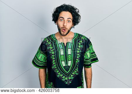 Handsome hispanic man wearing traditional african clothes scared and amazed with open mouth for surprise, disbelief face