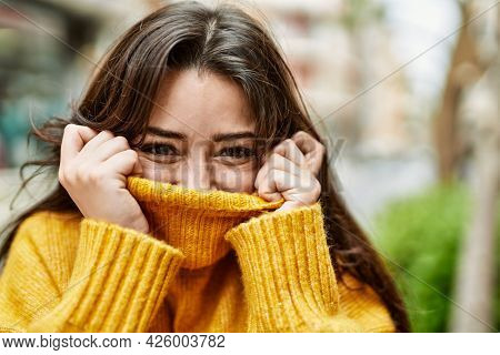 Young beautiful brunette woman wearing turtleneck sweater doing funny gesture covering face with sweater