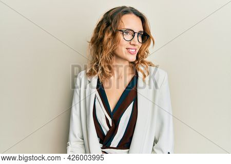 Young caucasian woman wearing business style and glasses looking away to side with smile on face, natural expression. laughing confident.