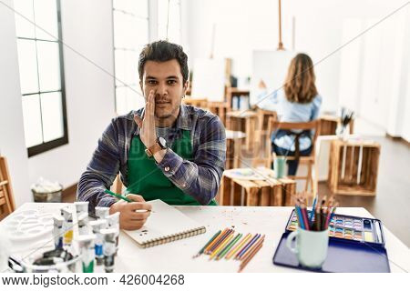Young artist man at art studio hand on mouth telling secret rumor, whispering malicious talk conversation