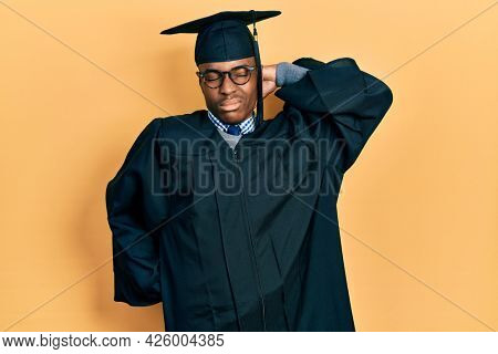 Young african american man wearing graduation cap and ceremony robe suffering of neck ache injury, touching neck with hand, muscular pain