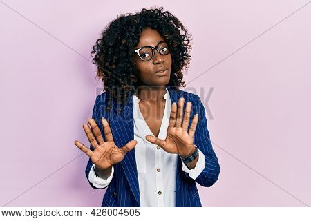 Young african american woman wearing business clothes and glasses moving away hands palms showing refusal and denial with afraid and disgusting expression. stop and forbidden.