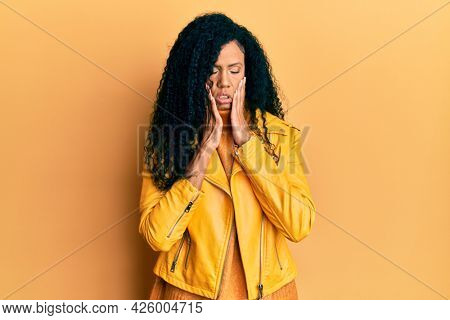 Middle age african american woman wearing wool winter sweater and leather jacket tired hands covering face, depression and sadness, upset and irritated for problem