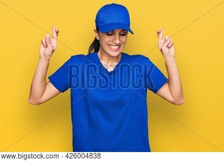 Young hispanic girl wearing delivery courier uniform gesturing finger crossed smiling with hope and eyes closed. luck and superstitious concept.