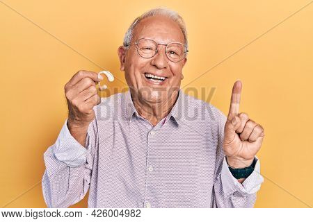 Senior man with grey hair holding medical hearing aid smiling with an idea or question pointing finger with happy face, number one