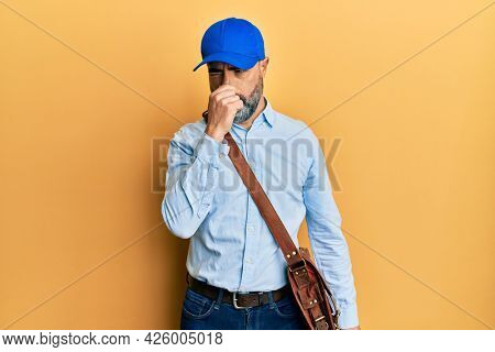 Middle age man with beard and grey hair wearing delivery courier cap smelling something stinky and disgusting, intolerable smell, holding breath with fingers on nose. bad smell